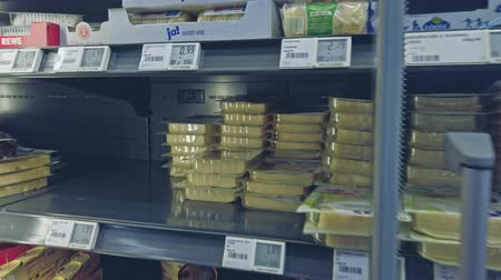 navegar : Bonn, Germany - 14 of Dec.,2019:interior shot of REWE supermarket POV. A man in fingerless gloves takes a packet of sliced cheese from the fridge.Its the exclusive brand Ja belongs to the REWEnetwork.