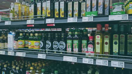concentrando : Bonn, Germany - 14 of Dec., 2019: interior shot of REWE supermarket in Bonn POV view. Many types of vegetable oil stands on the shelves - coconut, rapeseed, pumpkin and others 4k