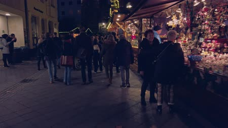 Bonn Germany, 23 Dec. 2019: People walking along the kiosks with christmas food in nighttime