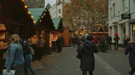 Bonn Germany, 23 Dec. 2019: People walk along the garlanded stalls of the Christmas market 4k slow motion