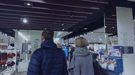 seçme : Bonn Germany, 23 Dec 2019: Inside the clothing store shoppers walk around shelves with goods POV clip