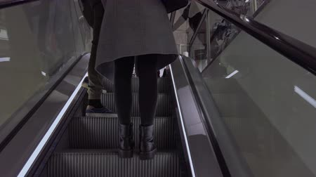 seçme : Bonn Germany, 23 Dec 2019: Couple rides escalator up and steps into clothing C-and-A store room POV clip