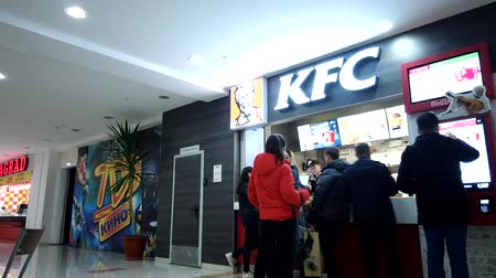 honger : Astrakhan, Russia, 20 Feb. 2020: People line up for buying KFC chicken at food court area in the mall motionlapse FHD