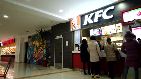 Astrakhan, Russia, 20 Feb. 2020: Motionlapse of people buying meal at KFC restaurant at food court area in the mall.