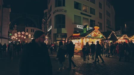 Bonn Germany, 23 Dec. 2019: Crowd of diverse people walk along the garlanded stalls of the Christmas market 4k slow motion