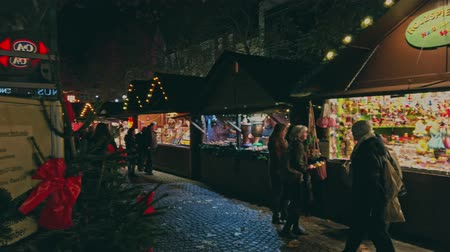 Bonn Germany, 23 Dec. 2019: Crowd of diverse people walk along the illuminated stalls of the Christmas market 4k slow motion