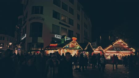 középkori : Bonn Germany, 23 Dec. 2019: Crowd of diverse people of Germany walk along the illuminated stalls of the Christmas market 4k slow motion