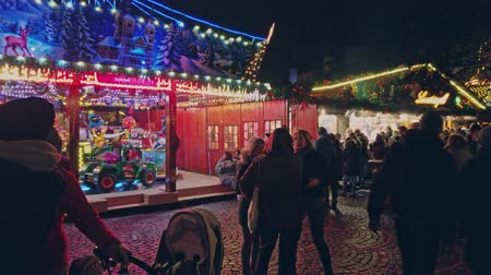 Bonn Germany, 23 Dec 2019: People walk at the Christmas market with a carousel 4k slow motion