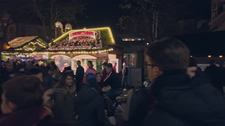 Bonn Germany, 23 Dec 2019: Blurred crowd of people at Christmas fair walking amid illuminated ferris wheel 影像素材