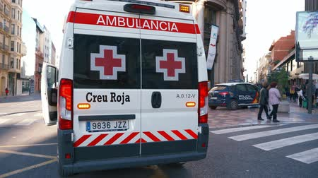 paramedics : Valencia, Spain, March 20, 2019: Paramedic getting into ambulance van. Red cross ambulance  and national police car. Responding  to emergency.