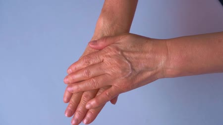krem : Woman applies Cream On Her Hands. Clean background. Slight slow motion.