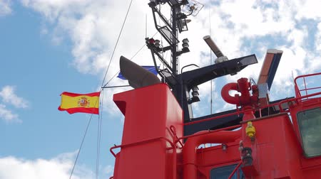 marine technology : Spanish Maritime Safety and Rescue ship moored to port, seen from the mooring. Safety and rescue operations, as well as protection of the maritime environment. Waving flag.