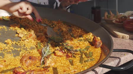 fogão : Chief woman putting paella from big pan on the  plastic plate . Spanish chicken pallella.