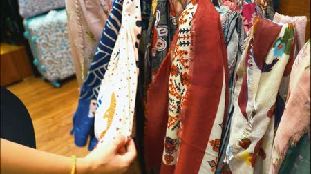 белье : Woman choosing silk and linen scarf at the shop. Variety of colorful woman scarfs. Стоковые видеозаписи