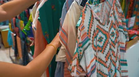 белье : Woman choosing  linen  blouse at the shop. Variety of light summer beach blouses.