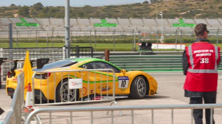 brasão : Tuned Yellow Ferrari 488 Challenge getting to the track.  Racing car. Ferrari Challenge 2019, Cheste, Spain.