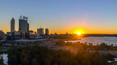 paisagem urbana : Time lapse Footage of beautiful dramatic Sunrise At Perth City, Australia With Zoom In Effect. Taken from Kings Park And Botanic Garden. Showing a clear sun rise from the horizon line. Zoom out. Vídeos