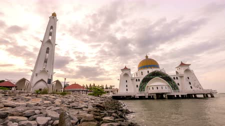masjid selat melaka : timelapse 4k footage of a beautiful sunrise at Melaka Strait Mosque with moving and changing color clouds. Panning.