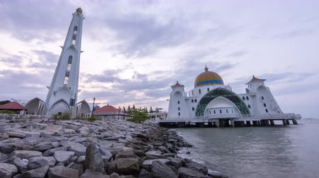 masjid selat melaka : timelapse 4k footage of a beautiful sunrise at Melaka Strait Mosque with moving and changing color clouds. Tilt up.