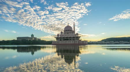 ислам : Time lapse 4k Footage of dramatic Sunrise At Putra Mosque, Putrajaya. Showing a moving and changing color clouds. Panning. Стоковые видеозаписи
