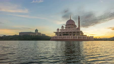 минарет : Time lapse 4k Footage of Beautiful Sunrise At Putra Mosque, Putrajaya. Showing a moving and changing color clouds. Tilt up.