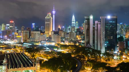 határkő : 4k footage time lapse of night scene at Kuala Lumpur city centre from a rooftop of a building, with city skyline, train, vehicle light trail. Panning