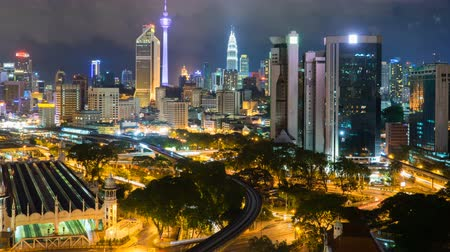 kuala lumpur skyline : 4k footage time lapse of night scene at Kuala Lumpur city centre from a rooftop of a building, with city skyline, train, vehicle light trail. zoom out Stock Footage