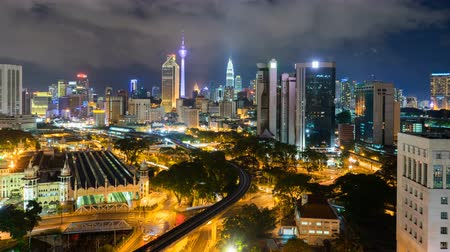 határkő : 4k footage time lapse of night scene at Kuala Lumpur city centre from a rooftop of a building, with city skyline, train, vehicle light trail. Stock mozgókép