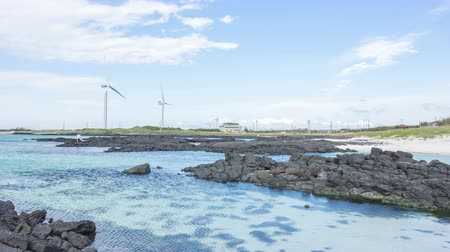 4k time lapse of beautiful beach with clear water and windmill at Jeju Island, South Korea.  zoom out Filmati Stock