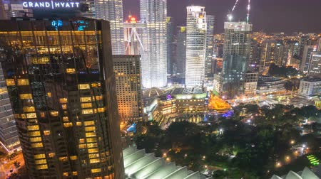 night scene : Time lapse of night scene at Kuala Lumpur city skyline with famous skyscraper landmark surrounding Petronas Twin Towers. Tilt up Stock Footage