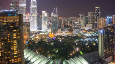 night scene : Time lapse of night scene at Kuala Lumpur city skyline with famous skyscraper landmark surrounding Petronas Twin Towers. Zoom out