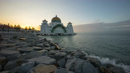 masjid selat melaka : Time lapse 4k Footage of Beautiful Sunrise At Malacca Straits Floating Mosque, or Masjid Selat Melaka. Showing a moving and changing color clouds. Pan right Stock Footage