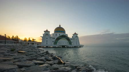 masjid selat melaka : Time lapse 4k Footage of Beautiful Sunrise At Malacca Straits Floating Mosque, or Masjid Selat Melaka. Showing a moving and changing color clouds. Tilt down