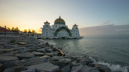 masjid selat melaka : Time lapse 4k Footage of Beautiful Sunrise At Malacca Straits Floating Mosque, or Masjid Selat Melaka. Showing a moving and changing color clouds. Tilt up