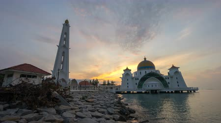 masjid selat melaka : Time lapse 4k Footage of Beautiful Sunrise At Malacca Straits Floating Mosque, or Masjid Selat Melaka. Showing a moving and changing color clouds. Pan left Stock Footage