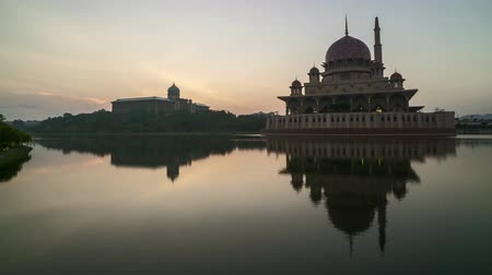 mesquita : Time lapse 4k Footage of Beautiful Dramatic Sunrise At Putra Mosque, Putrajaya with perfect reflection on the water. Tilt up