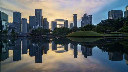 malásia : 4k time lapse of sunrise at Kuala Lumpur city skyline with reflection on water.