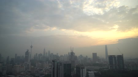 흐릿해진 : 4k establishing cinematic shot of sunrise blue hour hazy morning at Kuala Lumpur city skyline.