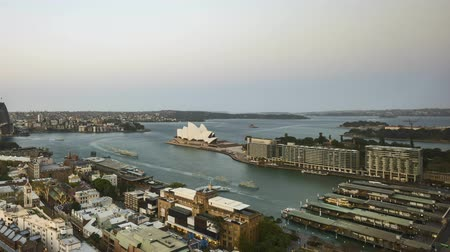 Сидней : 4k UHD time lapse of day to night to day (from sunset to sunrise) at Sydney city skyline, aerial view. Pan right Стоковые видеозаписи
