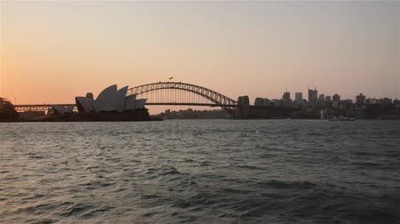 Австралия : 4k UHD cinematic establishing b roll shot of Sydney city skyline at harbour during sunset.