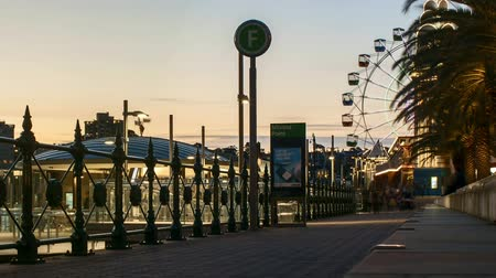 travel theme : Sydney, Australia - September 9, 2018: Time lapse of evening sunset scene at Milson Point Jetty with pedestrian walking and Luna Park Ferris Wheel.  Zoom out