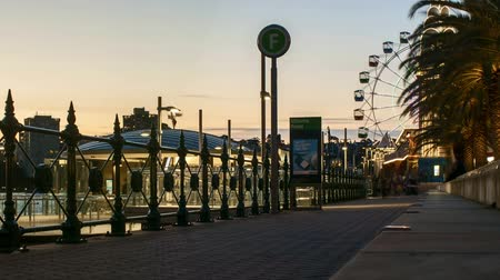 travel theme : Sydney, Australia - September 9, 2018: Time lapse of evening sunset scene at Milson Point Jetty with pedestrian walking and Luna Park Ferris Wheel.  Zoom in