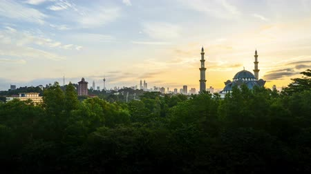 minaret : 4k UHD time lapse of sunset over silhouette mosque at Kuala Lumpur city skyline. Pan right Stock Footage