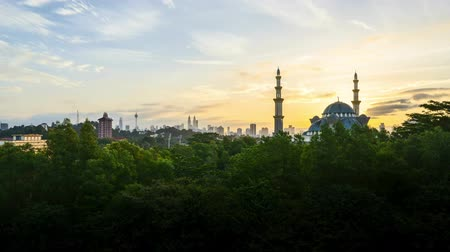 esquerda : 4k UHD time lapse of sunset over silhouette mosque at Kuala Lumpur city skyline. Pan left