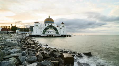 worship : Time lapse 4k Footage of Beautiful Sunrise At Melaka Straits Floating Mosque, or Masjid Selat Melaka with dramatic cloudy sky. Tilt down