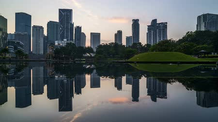 malajsie : 4k time lapse of sunrise at Kuala Lumpur city skyline with perfect reflection. Pan right