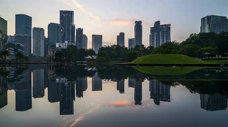 kuala : 4k time lapse of sunrise at Kuala Lumpur city skyline with perfect reflection. Zoom out