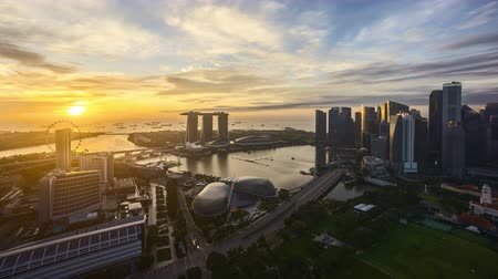 4k UHD time lapse of night to day sunrise scene at Singapore city skyline. Pan left Vídeos