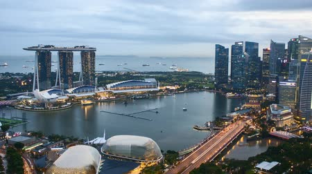 Time lapse of sunset day to night at Singapore Marina Bay skyline. Pan right
