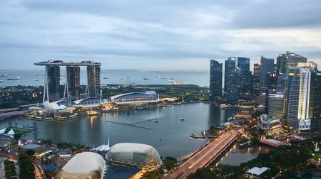Time lapse of sunset day to night at Singapore Marina Bay skyline. Tilt down